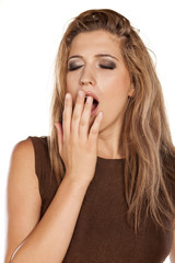 tired young woman yawning and holding hand over her mouth