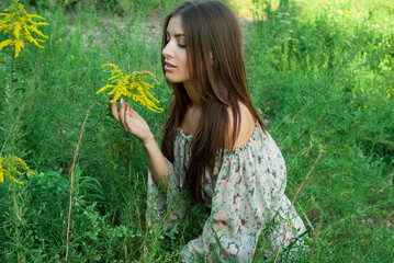 Nice girl inhales aroma of wild flowers