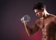 Muscular man lifting dumbbells on black background