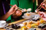 Fototapety Junge Leute essen Sushi in Asia Restaurant