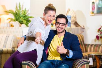 Paar kauft Sessel in Möbel Geschäft