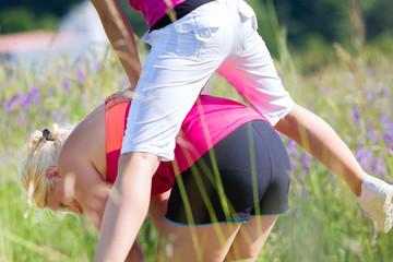 Frau und Mädchen beim Bockspringen im Feld