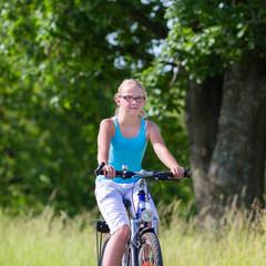 Kind fährt mit Fahrrad auf Feldweg