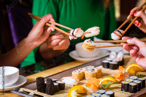 Leinwandbild Motiv Junge Leute essen Sushi in Asia Restaurant