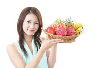 果物を持つ笑顔の女性