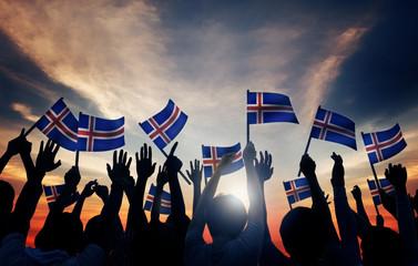 Group of People Waving Icelandic Flags in Back Lit