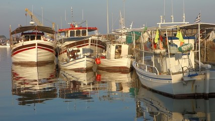 Fishing boats in port with reflections on sea water
