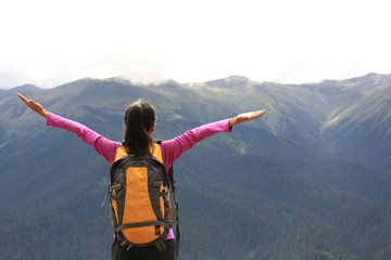 cheering young woman hiker  enjoy the view mountain peak