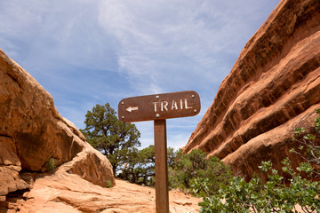 trail sign between sandstone cliffs
