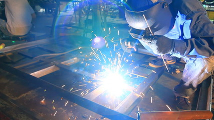 A worker welding in a factory as sparks fly