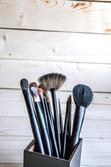 make-up brushes in a black glass