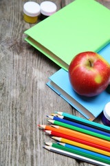 Books, pencils and an apple