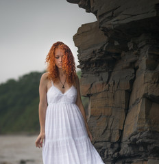 Beautiful redhead woman goes along the coast.
