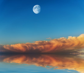 Moon with sunset sky reflected in water surface.