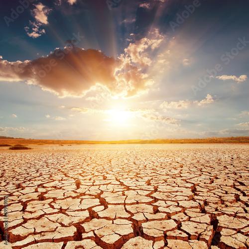 Leinwanddruck Bild red sunset over cracked earth