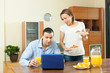 couple using laptop during breakfast