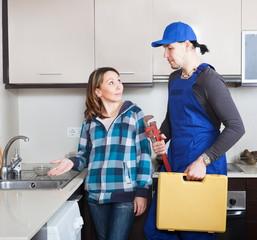 Adult repairman working at kitchen