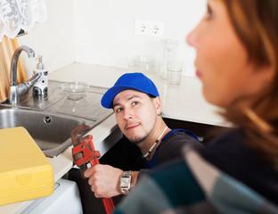 Girl watching as plumber working