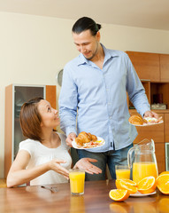 Smiling  couple having breakfast with juice