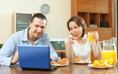 couple looking l in laptop during breakfast