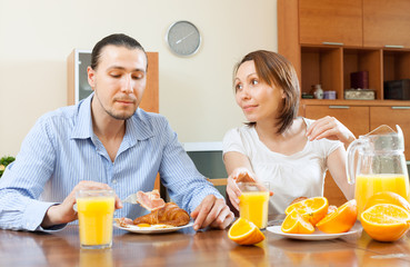 couple having breakfast with scrambled eggs and oranges