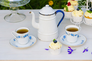 Tea with cupcakes in a vintage teapot