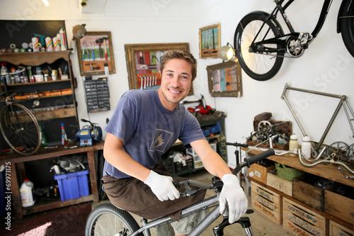 Deurstickers Portrait of smilng craftsman in bike workshop