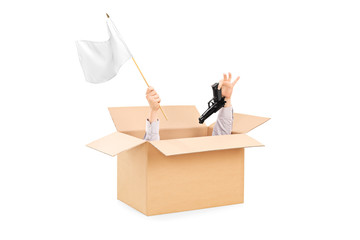 Male hands holding white flag and gun inside a box