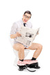 Joyful man reading the news seated on a toilet
