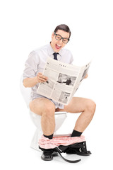 Joyful man reading the news seated on a toilet