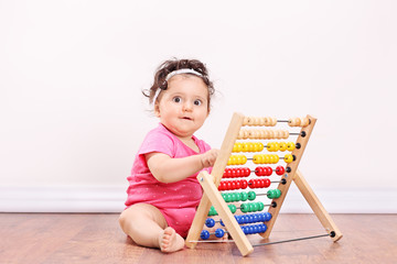 Little girl playing with an abacus seated on floor