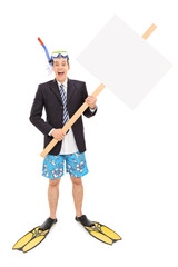 Businessman with snorkel holding blank signboard
