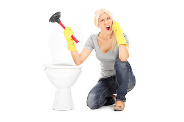 Angry woman holding plunger and talking on phone
