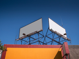 Blank white billboards on rooftop against blue sky background