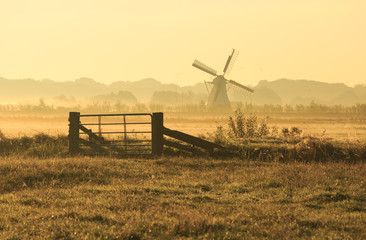 Fence and windmill in the Dutch countryside.