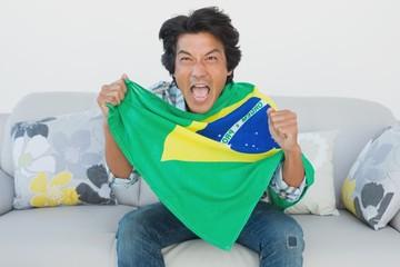 Brazilian football fan cheering while watching tv