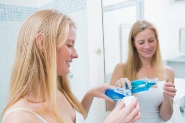 Happy woman pouring blue mouthwash
