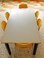 classroom with table and small chairs in kindergarten