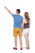 young couple in short pointing at wal