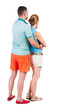 Back view of young embracing couple in shorts  hug and look.