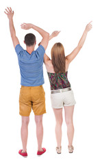 Back view of  joyful couple celebrating victory hands up.
