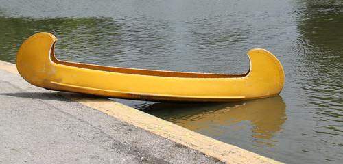 A Bright Yellow Fibre Glass Canoe Boat.