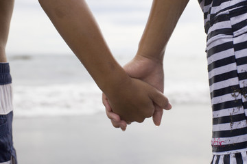 Holding Hands siblings on a sandy beach
