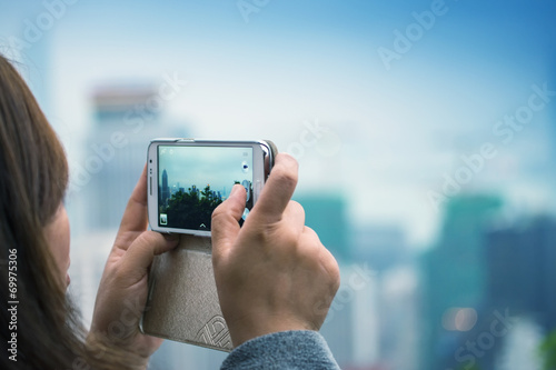 canvas print picture Woman taking city picture with her smartphone