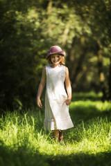 Mädchen mit Kleid und Hut in der Natur