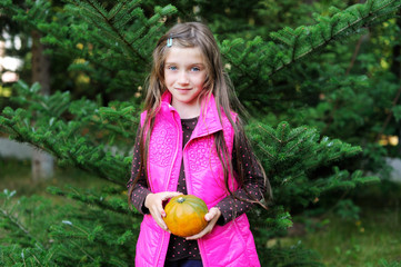 Kid girl holding little pumpkin