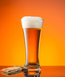 canvas print picture - Glass of beer with orange background