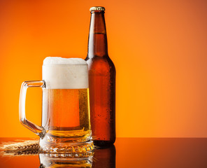 Glass and bottle of beer with orange background