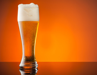 Glass of beer with orange background