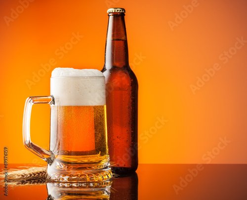 canvas print picture Glass and bottle of beer with orange background